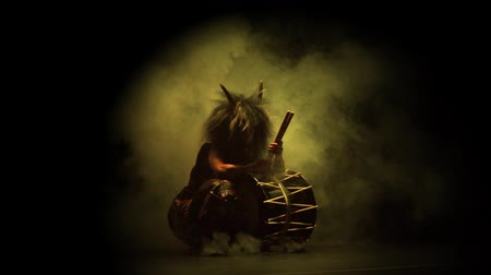 Taiko drummer in a wig and a demon mask on stage with drum on a black background and colorful smoke. Demon from Japanese mythology.