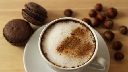hot beverage : Putting cinnamon into a cup of coffee on a wooden table with macaroons and hazelnuts HD