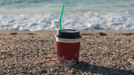 plastic cups : Bright paper cup of coffee on a sandy beach. Seashore