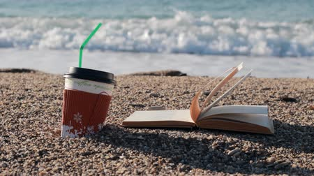 взятие : Reading a book and drinking a coffee near the sea