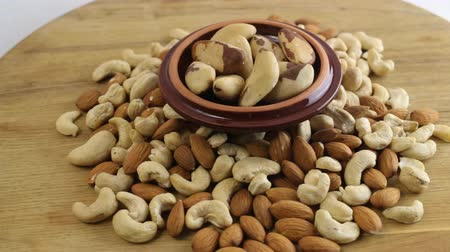misturado : Nuts background. Almond, cashew and brazilian nuts on wooden table Stock Footage