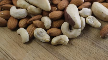 mandula : Close up shot of a pile of nuts rotating on wooden table