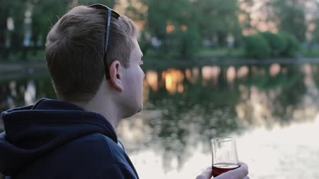 saborear : Man drinking wine sitting near the lake in the park Vídeos