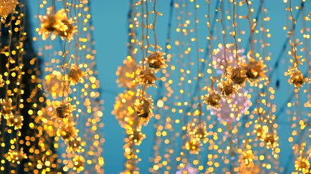 obbiettivo fotografico : Out of focus flashing color lights at Christmas night, soft defocused new year holidays light abstract background with bokeh balls. lens blur of bright winter party glittering lights of bulb garlands Filmati Stock
