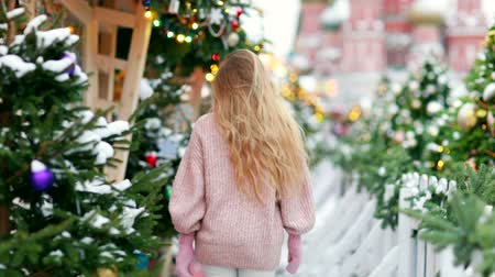 egyetlen virág : Blonde with long hair on a new years winter day on the background of a decorated city in the middle of a new years holiday Stock mozgókép