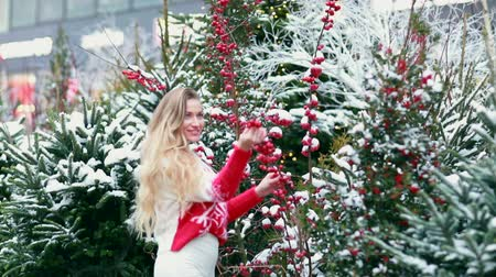 egyetlen virág : Girl on the street on the background of Christmas trees and red berries. Stock mozgókép
