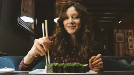 east asian food : Beautiful Caucasian woman eating sushi in a Japanese restaurant, and something interesting tells his girlfriend opposite