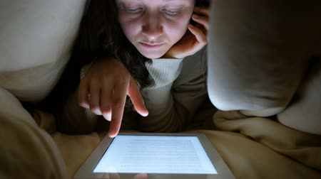 paplan : girl under a blanket looking at the tablet screen and turns the pages with your fingers, closeup Stock mozgókép
