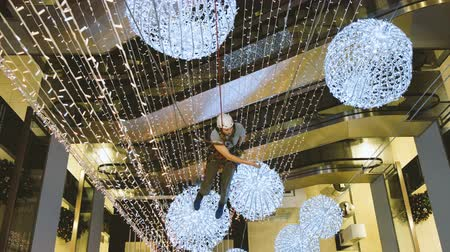 восемь : Industrial climber mounts Christmas decorations in the unsupported space in the shopping center Стоковые видеозаписи