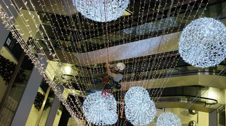bekap : Industrial climber mounts Christmas decorations in the unsupported space in the shopping center Stock mozgókép
