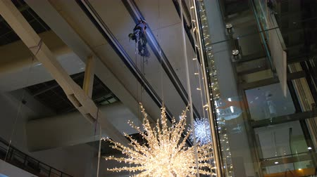 триггер : Industrial climber mounts Christmas decorations in the unsupported space in the shopping center Стоковые видеозаписи