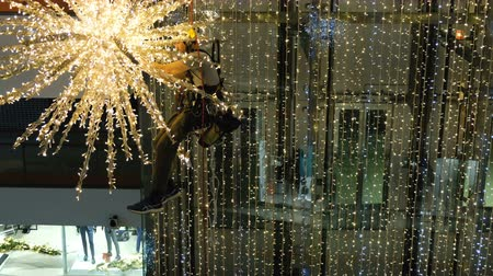 dağcı : Industrial climber mounts Christmas decorations in the unsupported space in the shopping center Stok Video