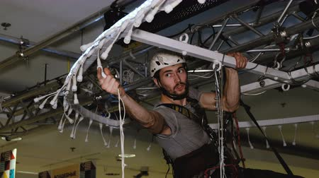 altura : Industrial climber sets up Christmas decorations in the shopping centre