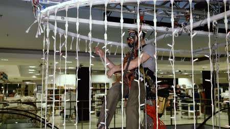 riskantní : Industrial climber sets up Christmas decorations in the shopping centre