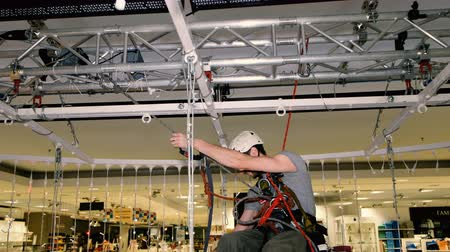 riskli : Industrial climber sets up Christmas decorations in the shopping centre