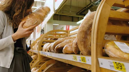 супермаркет : Girl sniffing fresh bread in a store, 4k.