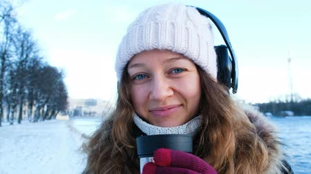 don : Beautiful young girl looking at the camera, listening to music and drinking tea from a flusk in the open air in winter, warmed in the park, portrait of a girl close-up, 4k. Stok Video