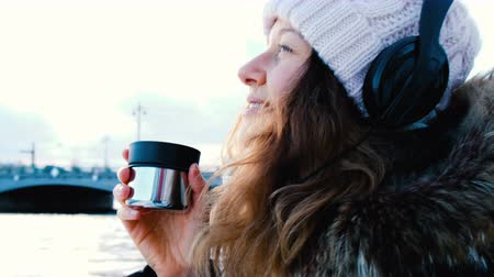 мороз : Young girl drinks hot tea or coffee outdoors, listening to music close-up, side view, 4k.