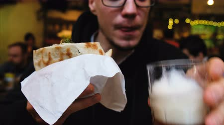 pita : Caucasian man eating falafel in pita and drinking beer, 4k.