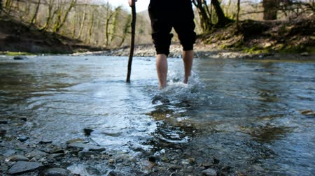 sztúpa : A young man crosses a mountain river wade barefoot with a stick, 4k.