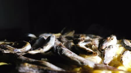 omega : Fish capelin with potatoes on a dark background stewed in a frying pan, slow motion.