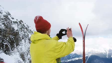 admires : The skier takes photos of the skis on the smartphone and a beautiful mountain view, 4k.