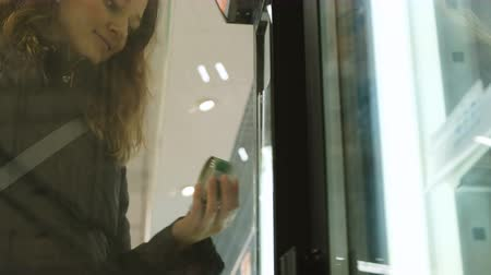 kaviár : Young woman is taking out of the refrigerator at the store canned closeup Stock mozgókép