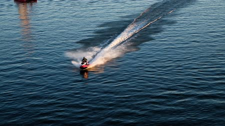 jet ski : Man riding a jet ski on the sea, turns and brakes on the water Stock Footage