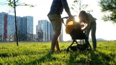 piknik : Parents sit down the baby in the stroller. Happy young family having a rest on nature in a park at sunset