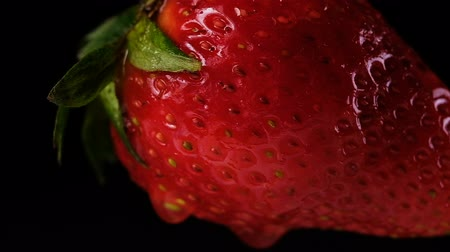waterdrop : Water flows down a strawberry close-up on a black background, slow motion Stock Footage