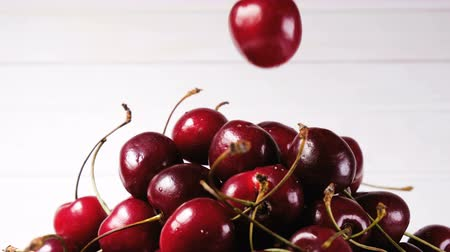 frutoso : Hand puts one cherry on top of a big heap on a white background