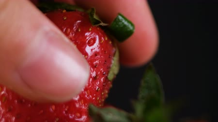 fruity garden : Man takes one strawberries on a dark background, close-up Stock Footage
