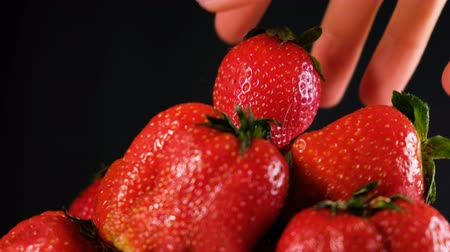 столовая гора : Man takes a strawberry on top of a big pile on a dark background, close-up Стоковые видеозаписи