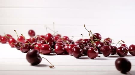 fruity garden : Ripe cherry berries fall down on a white background, slow motion