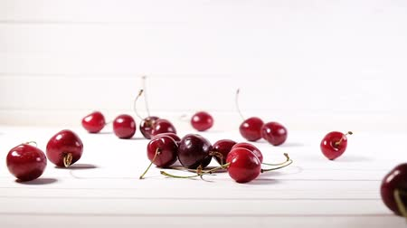 fruity garden : Cherry berries fall down on a white background, slow motion Stock Footage
