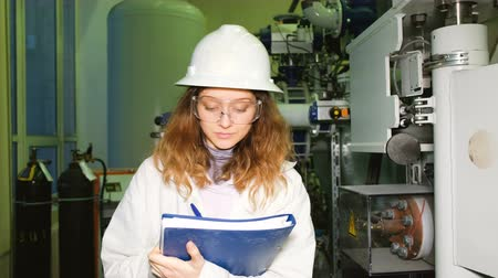 argon : A girl engineer in a white helmet and goggles records the data in a magazine, looks into the camera and smiles against the background of industrial gas equipment. Stock Footage