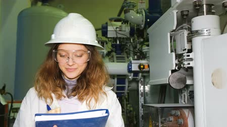 girl in robe : A girl engineer in a white helmet and goggles records the data in a magazine, looks into the camera and smiles against the background of industrial gas equipment. Stock Footage
