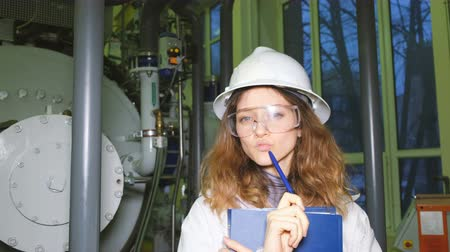 argon : Engineer girl in goggles and a white helmet thinks and looks at the camera, holds a pen and folder with papers, against the background of gas equipment.