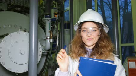 argon : A beautiful girl engineer in a white helmet thinks on the background of gas equipment, she got the idea and she wrote it down in a magazine. Stock Footage
