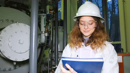 argon : Beautiful girl scientist doing a journal entry in a production lab, on a background of gas equipment, looking at the camera and smiling.