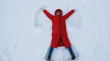 mentiras : Happy young woman doing a snow angel, top view Vídeos