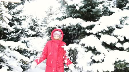 brotos : Cheerful young woman shoots snow from trees, jumps and shakes snow from a branch