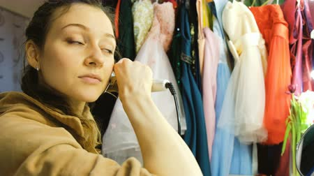 bodorítás : Young beautiful girl curls her hair on a curling robe in the dressing room