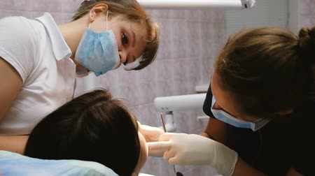 ücretli : Dentist and assistant treating the patients teeth in the dental office, slow motion. A young professional woman looking at the clients mouth Stok Video
