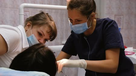 ücretli : Dentist doctor explains to a young assistant the treatment of teeth, slow motion. Client at the reception at the dentist Stok Video