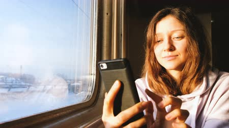 public transportation : Beautiful caucasian girl uses the phone on the train and looks out the window at sunset, 4k.