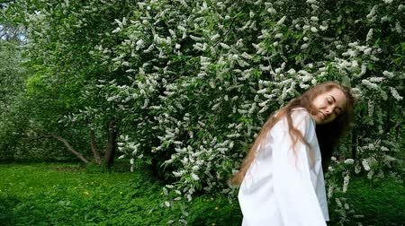 kudrlinky : Young beautiful long-haired beauty girl in a white shirt toss curly hair up and spinning in the background against a flourishing bird cherry tree, slow action. Girl model posing on camera