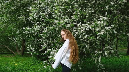 шелковистый : A young, long-haired beauty girl in a white shirt flips curly hair up and spinning in the background against a blossoming bird-cherry blossom, slow motion