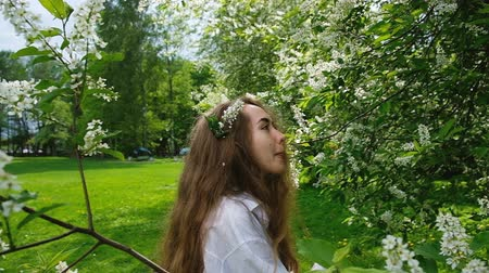 ninfa : Pretty European girl model posing on camera in blossoming bird cherry. A woman with long fluffy hair and a branch on her head is photographed in the park, slow motion