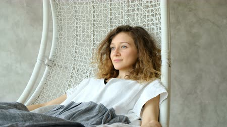 linen : Young European girl in a linen dress keep calm and swinging in a hammock chair, enjoying the rest. Beautiful girl dreams and swings in the loft interior of the house Stock Footage